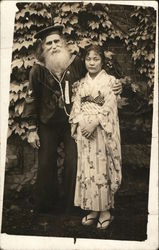 An older Sailor poses with a younger Japanese Woman dressed traditionally - Real Photo