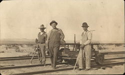 Three men building track for the railroad Circa 1900