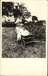 Four small children sit in a wagon in the backyard of a house (Early 1900's)