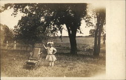 Young Girl with Doll Buggy in Yard
