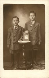 Two Boys Standing By Table With Book