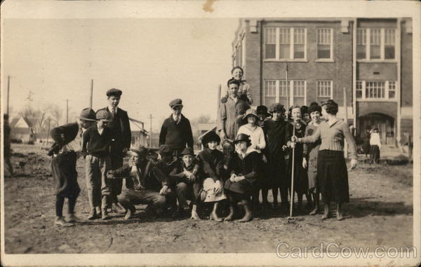 A group of young people pose playfully in front of an apartment building Early 1900's