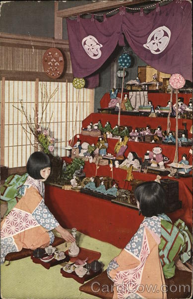 Two Asian Women Kneeling on Floor in Front of Large Doll Display