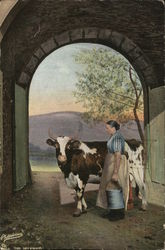 Woman Holding a Bucket Standing Next to Cow Beneath Archway