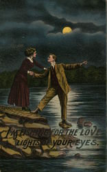 Man and Woman on Rocks Near Water With Moon Above