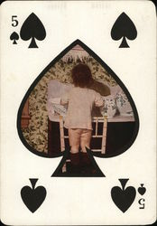 bare bottomed child inside a spade with a playing card theme