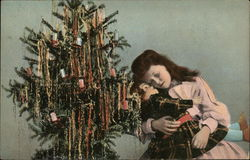 child hugging a doll in front of a Christmas tree