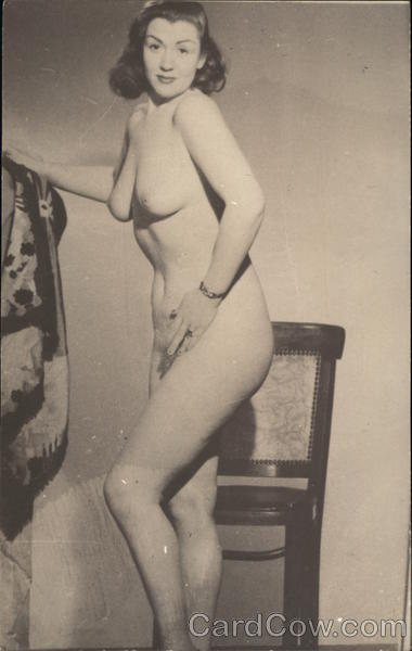 Nude woman posing in front of a chair Risque & Nude