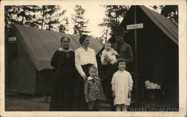 Soldier Posing with Family in front of Tents People in Uniform