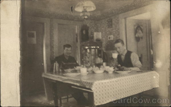two men eating a meal at a kitchen table