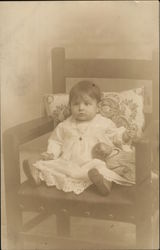 Baby Posing on a Chair with a Doll