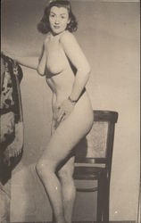 Nude woman posing in front of a chair
