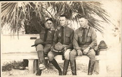 Three Soldiers on a Bench Under Palm Trees