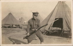 Soldier Posing With Rifle in Camp
