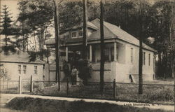 House with fence and two people near porch