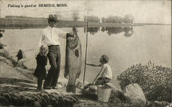 Man holding a giant fish with two children looking