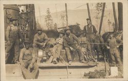 Seven Workmen with Logging Machinery and Timber in Background