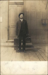 A man dressed in a suit carrying suitcases