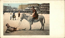 Man on Beach Holding Donkey With Woman Riding