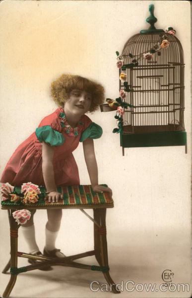 A Little Girl Leaning on a Table Next to a Bird Cage