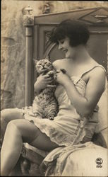 A Woman Sitting on a Bed Holding a Cat Postcard