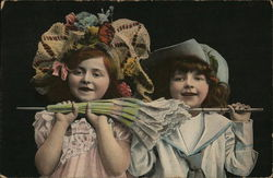 Two Young Girls Holding a Closed Umbrella