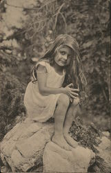 Young Girl with Long Hair Perched on a Rock Outdoors
