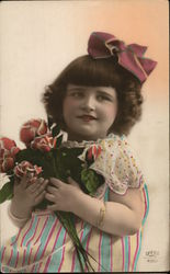 Little Girl Wearing Hair Bow Holding Red Flowers
