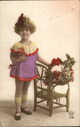 Little Girl Standing next to a Chair with Flowers