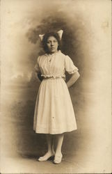 Young Woman in Dress with Bow in Hair
