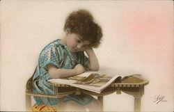 A Young Child Sitting at a Desk Reading a Magazine