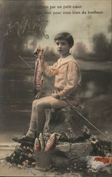 A young boy holding a fish and a fishing pole