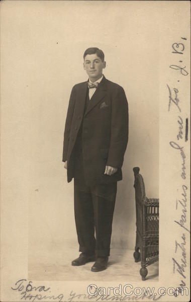 Young Man in Dark Suit Standing Near Furniture Men