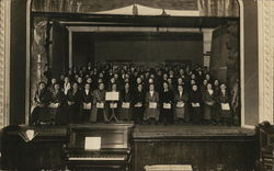 Large Choir in Multiple Rows on Stage Behind Piano