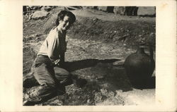 Person Leaning on Ground Near Large Pottery Piece