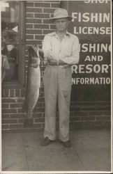 Man Holding 14-lb. Northern Pike Near Building