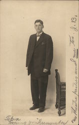 Young Man in Dark Suit Standing Near Furniture
