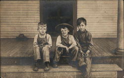 Three Boys Sit On A Wooden Porch