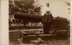 Woman Perched Atop Large Cannon in Park Setting