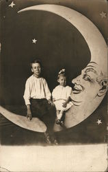Two Youngsters Seated on Paper Moon