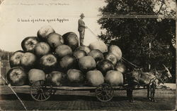 Farmer Standing on Pile of Giant Apples on a Cart
