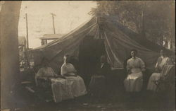 Four Woman and a Man Seated Near Large Tent