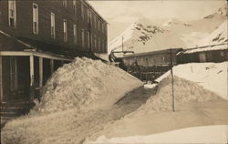 Building Near Mountains with Snow-Covered Walkway Shoveled Out