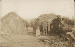 Man Standing Near Straw Huts and Wagon