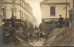 Men Standing Atop Dirt Piles Near Muddy Ditch in Street