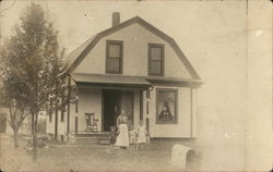 Mother and Three Young Children in Front of House