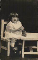 Girl Seated at Table with Blocks