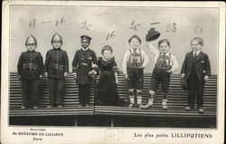 Seven Small People Standing in a Lineup Lilliputiens