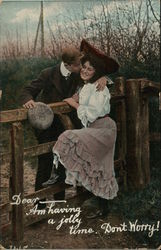 Young Man Embracing Smiling Young Woman Over Fence