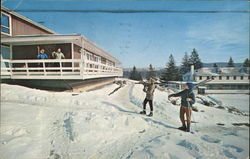 Two Skiers on a Slope Calling to Two People on Porch of an Inn